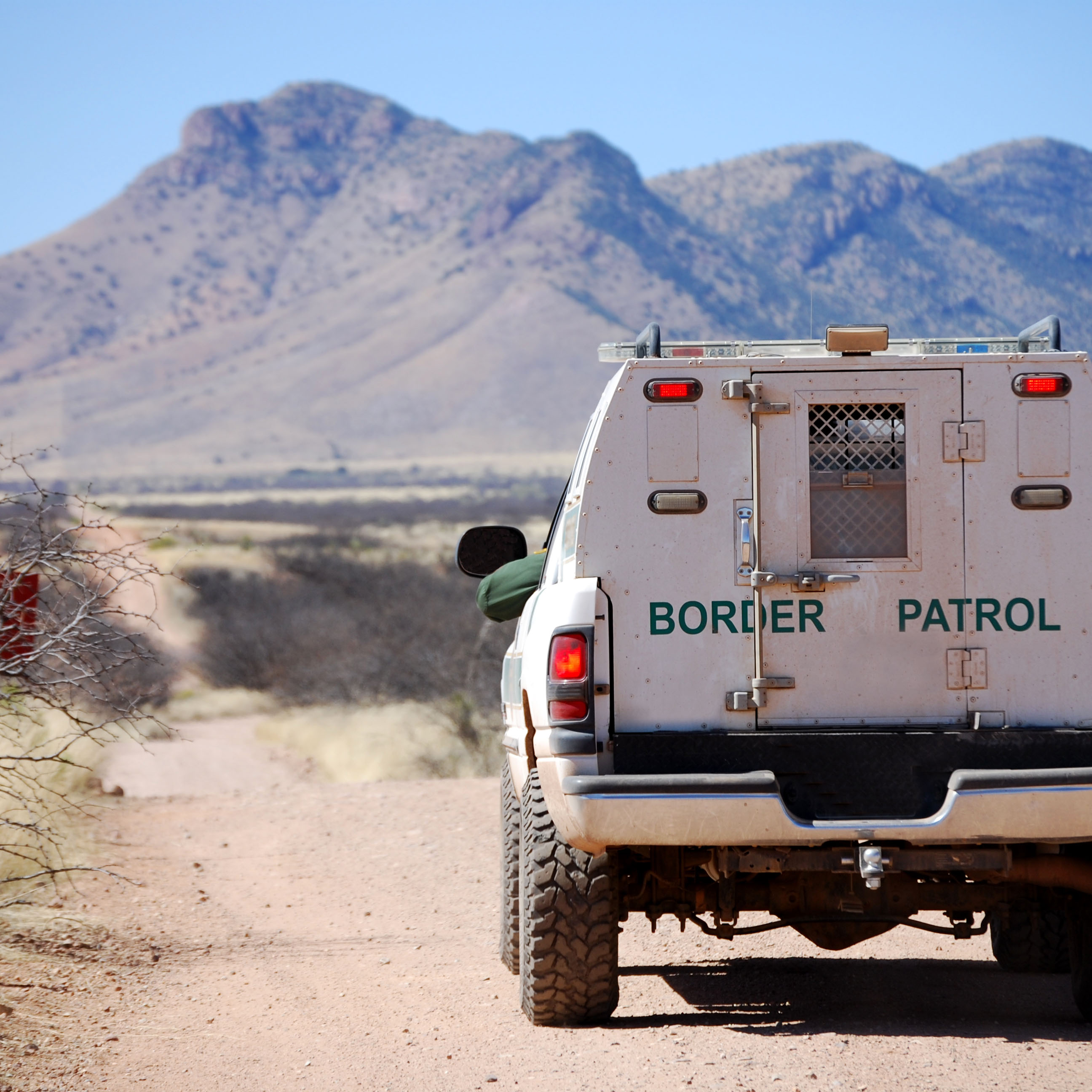 Back of a border patrol truck driving on a dirt road along the Mexican border in Arizona, with mountains in the background