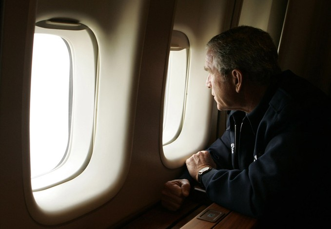 President Bush looks out the window of Air Force One inspecting damage from Hurricane Katrina while flying over New Orleans