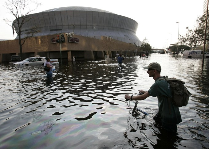 A man pushes his bicycle through flood waters near the Superdome in New Orleans after Hurricane Katrina left much of the city under water.